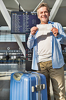 Portrait of happy mature man showing his boarding pass in airport