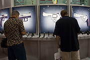 16 MAY 2009 -- PHOENIX, AZ: People look at handguns at the Taurus booth at the NRA convention in Phoenix Saturday. About 60,000 people were expected to attend the trade show at the 138th annual National Rifle Association Annual Meeting in the Phoenix Convention Center in Phoenix, AZ. Photo by Jack Kurtz