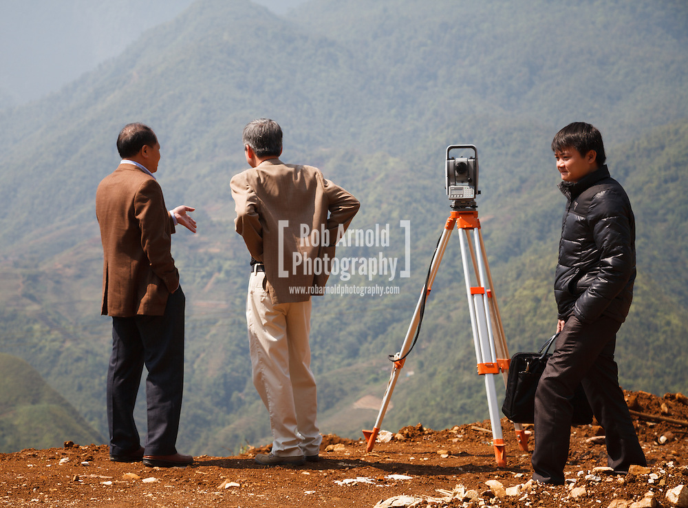 © Rob Arnold.  16/04/2013. Hanoi, Vietnam. Three men standing next to a total station as they collect data for a new building construction on the hillside in Sa Pa . Photo credit : Rob Arnold