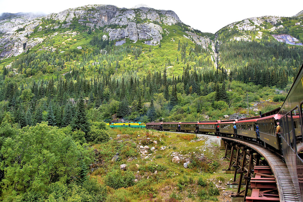 Train Turning through Coastal Mountains in Skagway, Alaska<br /> As the WP&YR chugs along the White Pass route through the stunning coastal mountains, most tourists elect to enjoy the marvelous views from the comfort of their window seats. Those determined to photograph the excursion jostle for position outside on small platforms between the parlor cars. You know where I was standing for the whole ride.