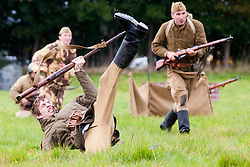 """Re-enactors portray Soviet soldiers from the Russian 13th Guards Rifle Division """"Poltavaskaya"""" take part in a battle reenactment Battle reenactment on day two at the Showground Pickering<br /> 13 October 2012<br /> Image © Paul David Drabble"""