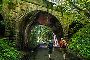 Hike under old bridge in North York Moors NP. England, UK, Europe. Today we toured North York Moors National Park from Grosmont to Robin Hood's Bay on foot and via van, plus Whitby on the Esk River, in North Yorkshire county, England, United Kingdom, Europe. England Coast to Coast hike with Wilderness Travel, day 13 of 14. We walked a rural path through bracken, purple blooming heather moors, and farmland before descending cliffs to the beach and village of Robin Hood's Bay. We dipped our boots into the North Sea, having completed our journey via foot and car from the Irish Sea over two weeks. Lunch at Wainwrights Bar at the Bay Hotel. Visit spectacular Whitby Abbey and the seaside fishing port of Whitby. Overnight at Best Western Forest & Vale Hotel, in Pickering, North Yorkshire. [This image, commissioned by Wilderness Travel, is not available to any other agency providing group travel in the UK, but may otherwise be licensable from Tom Dempsey – please inquire at PhotoSeek.com.]