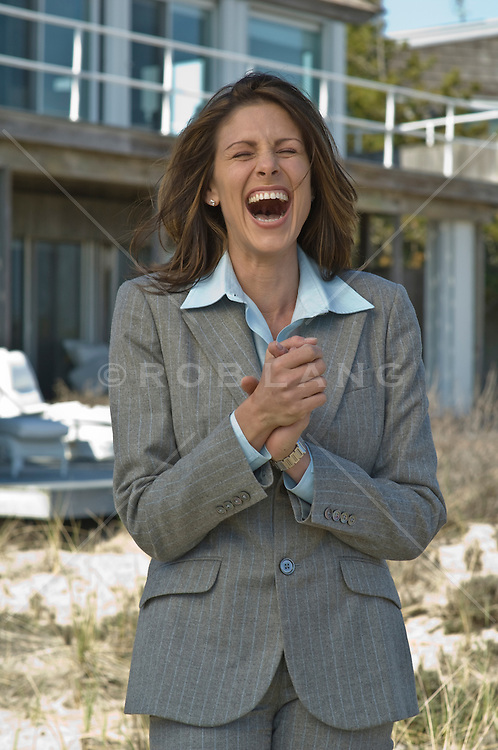 Woman laughing while standing outside in front of a house in East Hampton, NY