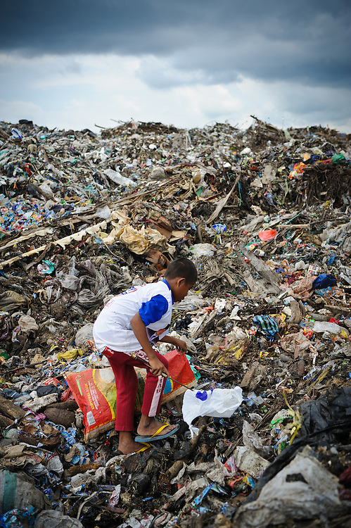 Idris, 13, collecting plastic and metal waste for recyling at the 'Trash mountain', Makassar, Sulawesi, Indonesia.