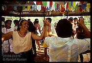 Women dance in a circle in pavilion at Festa Junina (June Fest) celebration on Carvalho ranch near Eirunepe, Brazil.