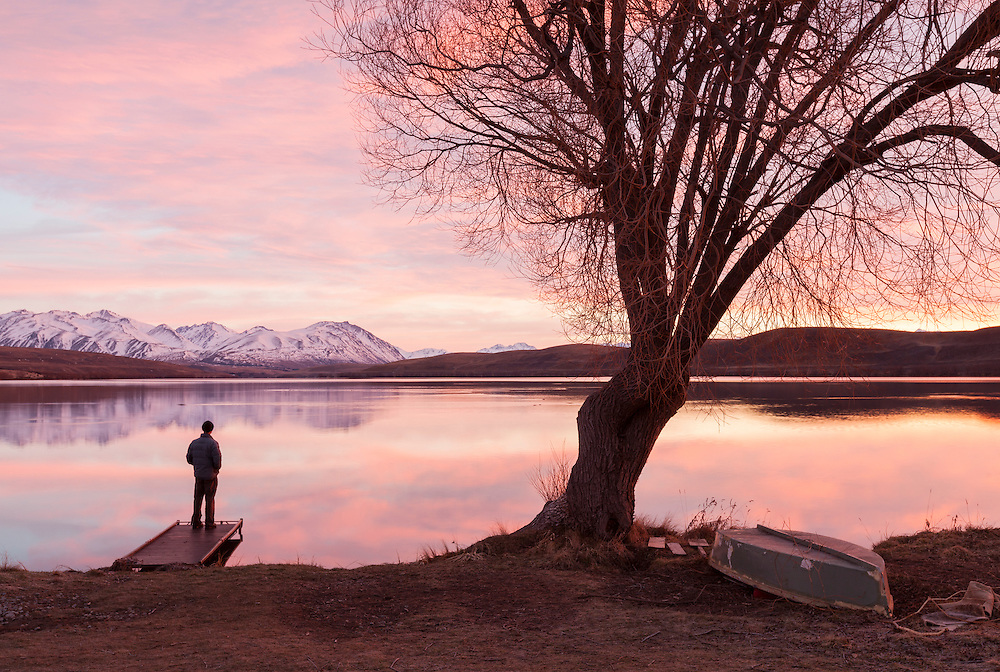 A man stands on a jetty looking out at a colourful dawn over Lake Alexandrina. The southern end of Lake Alexandrina has a collection of tiny holiday cottages.
