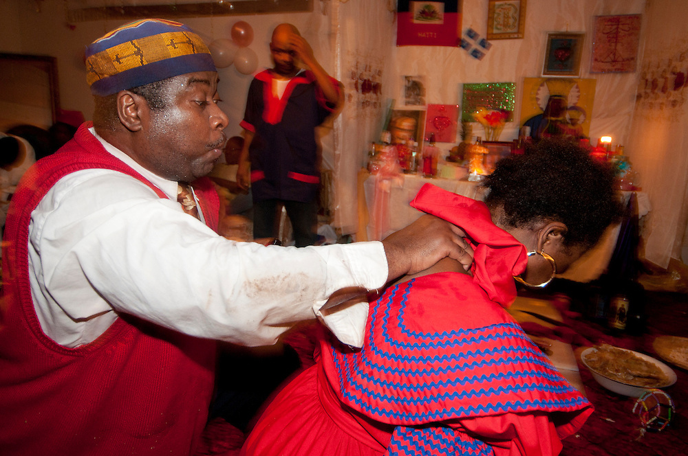Vodou ceremony during the winter solstice in a suburbs of Montreal. The Mambo finish the ceremony with Foula by spiting some water to call the spirits