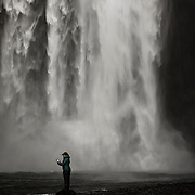 Woman reading a Kindle at Skogafoss waterfall, Iceland