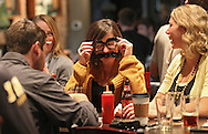 Kaitlin Oswood (center) of Cedar Rapids laughs as she puts on a pair of glasses with a mustache at a Movember get together during the Iowa football game at Dublin City Pub in Cedar Rapids on Saturday, November 17, 2012.