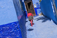 A girl in red walks up stairs in the old town (medina) of Chefchaouen in Morocco.