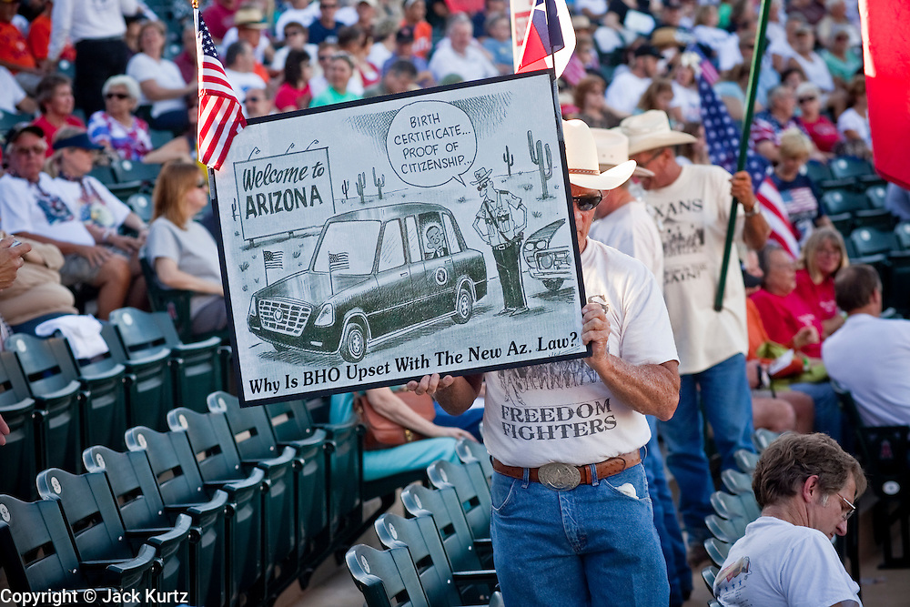 "May 29 - TEMPE, AZ: A man with an anti-Obama cartoon at a Tea Party rally in Tempe, AZ. About 3,000 people attended a ""Buy Cott Arizona"" rally at Tempe Diablo Stadium in Tempe, AZ Saturday night. The rally was organized by members of the Arizona Tea Party movement to show support for Arizona law SB1070. The ""Buy Cott"" is a reaction to the economic boycott planned by opponents of SB1070. SB1070 makes it an Arizona state crime to be in the US illegally and requires that immigrants carry papers with them at all times and present to law enforcement when asked to. Critics of the law say it will lead to racial profiling, harassment of Hispanics and usurps the federal role in immigration enforcement. Supporters of the law say it merely brings Arizona law into line with existing federal laws.  Photo by Jack Kurtz"