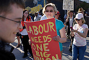"Windsor, Ontario, 2013. Mireille Coral holds a pro labour sign during the procession of the annualMay Day march. The annual march has a novel ""Living Museum"" concept where historical union envents are re-enacted along the route."