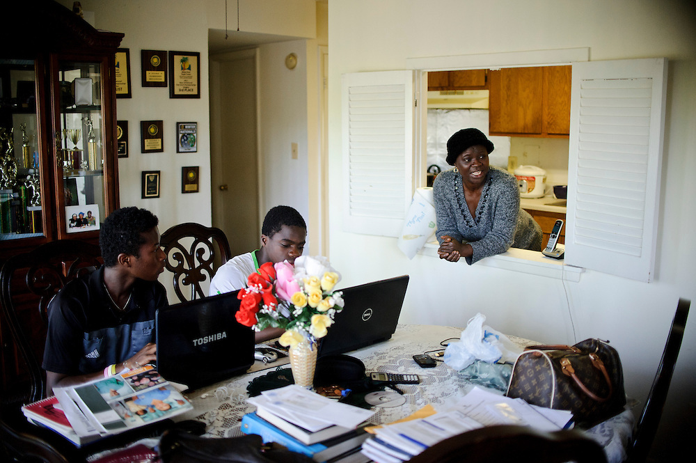 photo by Matt Roth.Friday, May 11, 2012.Assignment ID: 30125820A..Kenneth Downing, 16, left, and Francis Tiafoe, the top-ranked 14-year-old tennis player in the country, middle, play on their laptops while Francis's mother Alphina Kamara pokes her head out of the kitchen to socialize while making dinner. ..His father immigrated from Sierra Leone in 1996. Francis's father, Constant lived where he worked at the Tennis Center at College Park, where Francis and his twin brother Franklin would occasionally sleep. Misha Kouznetsov, a tennis pro at the Center saw potential in Francis and has been training the twins since they were eight. Constant and his family have since moved into an apartment five minutes away, and the boys train and go to school full-time at the Center.
