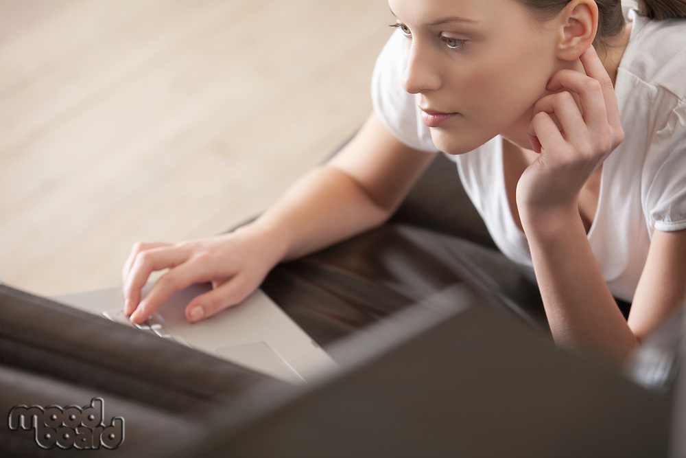 Young woman lies on leather sofa working on laptop