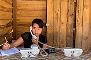 02 MARCH 2014 - MYAWADDY, KAYIN, MYANMAR (BURMA):  A woman who operates a phone stand takes messages for customers in her shop in Myawaddy, Myanmar. Most people in Myawaddy don't have phones yet. Myawaddy is separated from the Thai border town of Mae Sot by the Moei River. Myawaddy is the most important trading point between Myanmar (Burma) and Thailand.  PHOTO BY JACK KURTZ