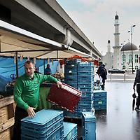 Nederland, Amsterdam , 19 augustus 2014.<br /> Markt in Amsterdam ZuidOost bij Kraaiennest.<br /> Kraaiennest is een station van de Amsterdamse metro, gelegen op een viaduct boven de Karspeldreef in het stadsdeel Amsterdam Zuidoost. Het bovengrondse metrostation opende op 14 oktober 1977 en maakt deel uit van Gaasperplaslijn 53.<br /> Een marktman ruimt zijn kraam op aan het einde van de middag.<br /> Foto:Jean-Pierre Jans