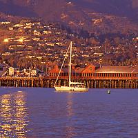 View of Santa Barbara's harbor and wharf area with the sun setting on the Riviera neighborhood