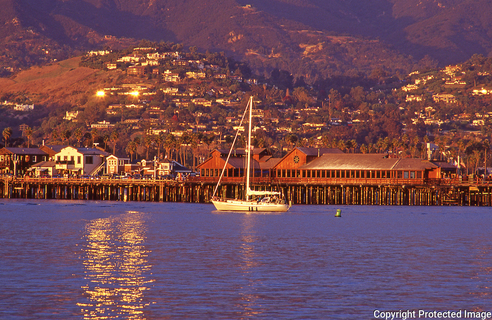 View of Santa Barbara's harbor and wharf area with the sun setting on the Riviera neighborhood