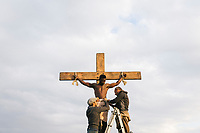 """MATERA, ITALY -6 OCTOBER 2019: Costume and set designers are seen here preparing the crucifixion of the impenitent thief (on the left of Jesus Christ) during the production of """"The New Gospel"""", a film by Swiss theatre director Milo Rau, in Matera, Italy, on October 6th 2019.<br /> <br /> Theatre Director Milo Rau filmed the Passion of the Christ  under the title """"The New Gospel"""" with a cast of refugees, activists and former actors from Pasolini and Mel Gibson's films.<br /> <br /> The role of Jesus is performed by Yvan Sagnet, a Political activist born in Cameroon and who worked on a tomato farm when in 2011 he revolted against the system of exploitation and led the first farm workers' strike in southern Italy. In a series of public shoots in the European Capital of Culture Matera, Jesus will proclaimed the Word of God, was crucified (October 6th 2019) and finally rose from the dead in Rome, the capital of Catholic Christianity and seat of one of the most xenophobic governments in Europe (October 10th 2019).<br />  <br /> Parallel to the film, the humanistic message of the New Testament was transformed into the present: at the beginning of September, the campaign """"Rivolta della Dignità"""" (Revolt of Dignity), which demanded fair working and living conditions     for refugees, global freedom of travel and civil rights for all, started with a march from the southern Italian refugee camps. """"It's about putting Jesus on his feet,"""" director Milo Rau said. Led by Jesus actor Yvan Sagnet, the campaign fights for the rights of migrants who came to Europe via the Mediterranean to be enslaved by the Mafia in the tomato fields of southern Italy and to live in ghettos under inhumane conditions. The campaign and the film thus create a """"New Gospel"""" for the 21st century, a manifesto of solidarity with the poorest, a revolt for a more just and humane world."""