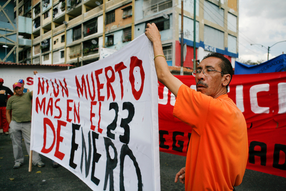 People march at a demonstration organized by different collectives in 23 de Enero to protest the internal violence happening inside the barrio. Violence still continues to plague the city which is considered one of the most dangerous in the world. Many of Chavez's supporters feel the government has not addressed the issue enough, and therefore feel they must combat violence on their own and through collectives in the barrios.