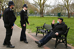 © Licensed to London News Pictures. 03/04/2020. London, UK. Police officers speak with a man wearing a face mask in Duckett's Common as they patrol Wood Green High Road in north London. The Government has ordered that people should go out only for food and health reasons or for work, and keep 2 meters away from other people at all times to slow the spread of the virus and reduce pressure on the NHS. Photo credit: Dinendra Haria/LNP