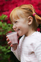 Young girl (5-6) drinking smoothie smiling
