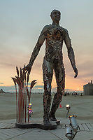 Passage by: Dana Albany from: San Francisco, CA year: 2018<br /> <br /> Passage is an installation of a man, in a captive gesture, leisurely walking while its hand sweeps through stalks of wheat. The sculpture clearly highlights characteristics of a human form; muscle, sinuous tendon, sculpted hands, feet. Yet, it's a composite of mechanical debris and steel. Viewers may hypothesize, is this a man? is it part robot? and what is the blurry fine-line between each? The other huge component is the presence of the wheat. It symbolizes abundance, life, fertility. It is food, subsistence, of which without, the human race would be extinct. Viewers can look closer at the inherent beauty of the human form, contemplate mechanics/technology or most importantly, be reminded of our absolute reliance on nature in the end. My Burning Man 2018 Photos:<br />