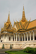 """Throne Hall, Royal Palace, Phnom Penh, Cambodia. The Khmer name for the Throne Hall is Preah Thineang Dheva Vinnichayyeaah meaning the """"Sacred Seat of Judgement."""" The Throne Hall is where the king's confidants, generals and royal officials once carried out their duties. It is still in use today as a place for religious and royal ceremonies (such ascoronations and royal weddings) as well as a meeting place for guests of the King. The cross-shaped building is crowned with three spires. The central, 59 meter spire is topped with the white, four-faced head of Brahma. Inside the Throne Hall contains a royal throne and busts of Cambodians kings of the past.This Throne Hall is the second to be built on this site. The first was constructed of wood in 1869-1870 under King Norodom. That Throne Hall was demolished in 1915. The present building was constructed in 1917 and inaugurated by King Sisowath in 1919. The building is 30x60 meters and topped by a 59-meter spire"""