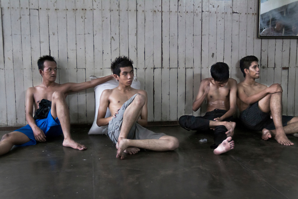 "Four young fighters take a break from Burmese kick boxing ""Lethwei"" training session at the YMCA Yangon  in Myanmar."