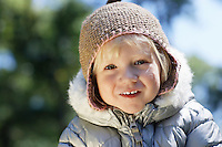 Portrait of young girl (3-4) in winter clothes outdoors
