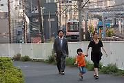 A woman with a young boy and a young office worker or salaryman walk near train tracks in Nakameguro, Tokyo, Japan. Wednesday, May 20th 2009