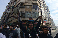 Aleppo, Syria, December, 2012.- After prayers a rebel fighter, called Katibas, raises his Kalishnikov and his son at a rally to protest the Assad regime and show support for the Free Syrian Army. (Photo by Miguel Juárez Lugo)