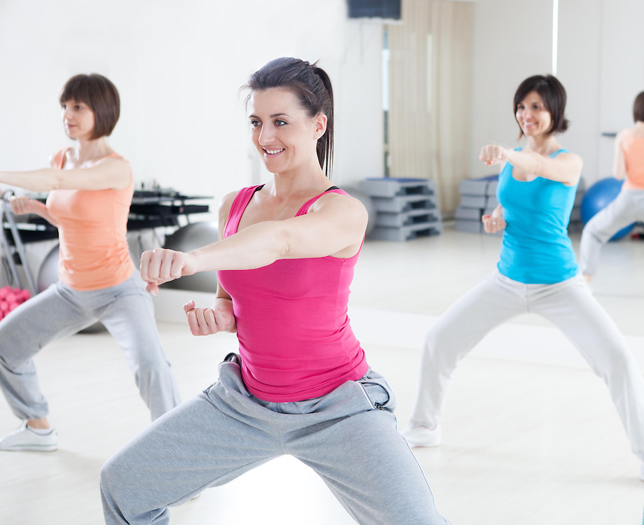 Smiling women doing punch on aerobic class in fitness gym.