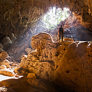 A caver viewing the light entering the Tham Mae Usu cave in Northern Tak province, Thailand. The cave is only accessible during the dry season of Thailand as the main entrance is through the mae Usu river that flows out of this limestone karst cave, making it impassable throughout most of the year.