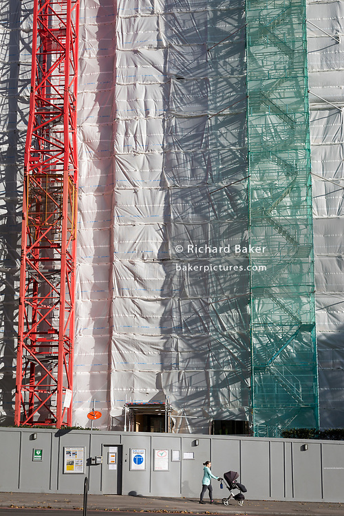 A construction worker climbs a tall gantry tower next to a crane tied to the side of an office building (formerly Express Newspapers) being renovated at the southern end of Blackfriars Bridge, on 27th October 2017, in London, England.
