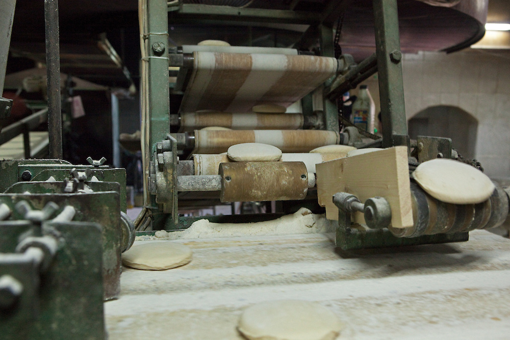 Traditional flatbread rolled out into circles before being baked in a small bread factory, Aleppo
