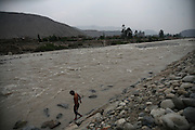 A youth walks by the edge of the Rimac river in Chosica, Lima, Peru March 18, 2009. The Rímac River is the most important source of potable water for Peru's capital, actually a plot of desert in the western Pacific edge. It runs down through nearly 160 kilometers from the snowy peaks of the Huarochiri province to the port of Callao, one of Pacific Rim's most important raw materials exporter's ports. The country has approved a new law regulating water property and utilization that several social organizations claim will affect the health of the riverside population and the capital's water quality, opening the path to privatization and making the control over the river basins too flexible. With the Rimac river serving nearly 6 million people in the Lima metropolitan area itself Peruvians have reasons to be suspicious. Their biggest water source has been systematically contaminated by mining projects in the high river basin resulting in the introducing of plumb and arsenic among other metals in the food chain. Also nearly 35% of the food traded in Lima carries higher than allowed levels of fecal coliforms due to untreated waste water from informal settlements being used as irrigation.
