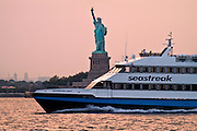 Sea Streak passenger boat passes by Lady Liberty on the way to New Jersey.