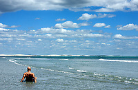 man sunbathing in the water of the beach in the beautiful fisherman village of Jericoacoara in ceara state brazil