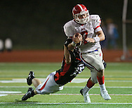 Linn-Mar's Austin Burbridge (15) pulls down Washington's Charles Blades (7) during the second quarter of the game between Cedar Rapids Washington and Linn-Mar at Linn-Mar Stadium in Marion on Friday, September 14, 2012.