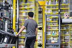 """© Licensed to London News Pictures . 04/12/2019. Manchester , UK . Newly delivered stock is sorted and scanned before being placed on to robotic containers for storage in the warehouse . Inside the """"MAN1"""" Amazon fulfilment centre warehouse at Manchester Airport in the North West of England . Photo credit : Joel Goodman/LNP"""