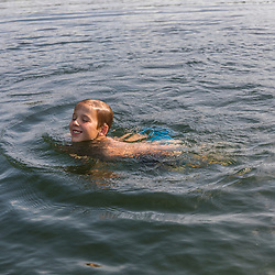 A boy swimming in Island Pond at Red River Camps in Aroostook County, Maine. Deboullie Public Reserve Land.