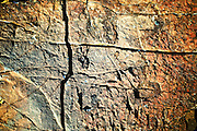 Detail of incised pattern in rock face, Wadi El Ain, Oman.  A Cross and a curve in layers of orange and silver colors makes an abstract design