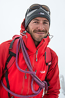 A portrait of a smiling male mountaineer on a clody day in Mont Blanc Massif.
