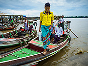 22 NOVEMBER 2017 - YANGON, MYANMAR: A passenger steps off a river taxi at a pier on the Twante Canal in Yangon. The small boats shuttle passengers across the canal or up and down the canal to other piers in Yangon.    PHOTO BY JACK KURTZ