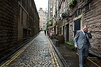 Man breaks from party to take cell phone call in downtown Edinburgh, Scotland. Copyright 2019 Reid McNally.