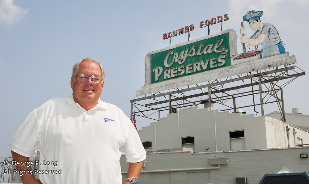 Al Baumer Jr. and the Crystal Preserves sign above Baumer Foods in New Orleans on August 4, 2004