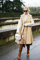 Tatiana Korsakova wears a sleeveless beige trench coat, brown boots, a bag, a white wool off shoulder top, outside Valentino, during Paris Fashion Week Womenswear Fall/Winter 2018/2019, on March 4, 2018 in Paris, France.  (Photo by Nataliya Petrova/NurPhoto/Sipa USA)