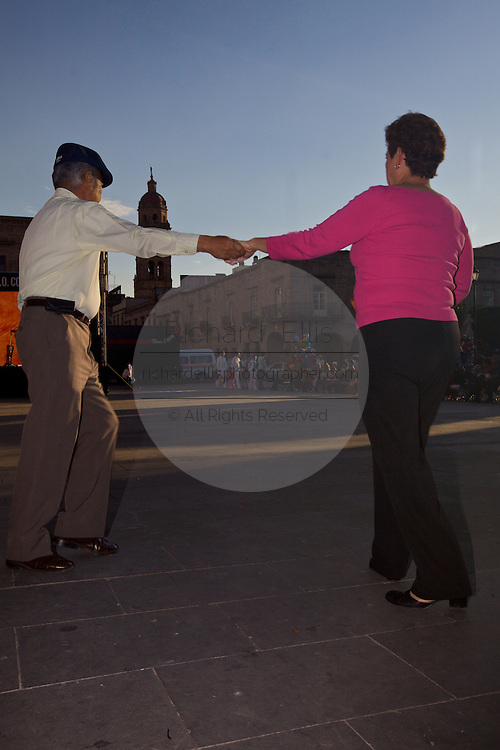 A couple dance in the Plaza de Armas Morelia with a view in the background of Templo de los Agustinos, in the central highland city of Morelia, Michoacan state Mexico. The city is a UNESCO World Heritage Site and hosts one of the best preserved collection of Spanish Colonial architecture in the world.