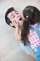 Playful daughter on top of father at home
